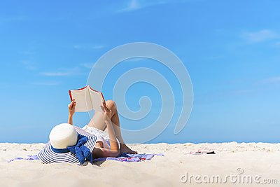 Woman laying and reading on the beach with blue sky in summer times.