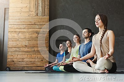 stock image of young women and men in yoga class, relax meditation pose