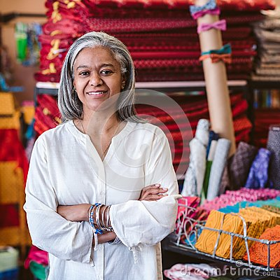Smiling mature woman standing by textiles in her fabric shop