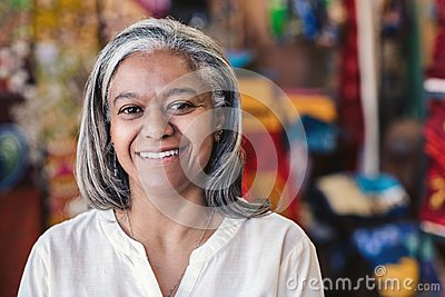 Smiling mature woman standing in her colorful clothing shop