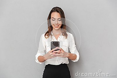 Portrait of a happy young business woman using mobile phone