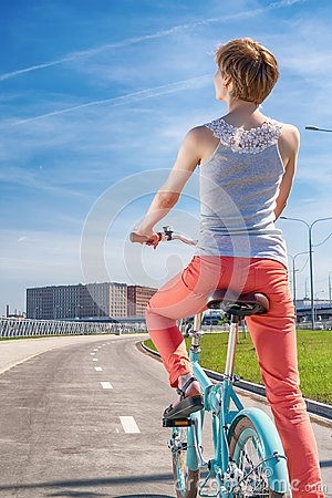 Girl riding on blue folding bike looking at bright cityscape