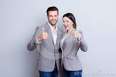 Two smiling happy businesspeople in formalwear showing thumbs-up on gray background