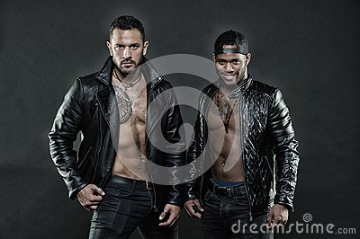 Machos with muscular torsos look attractive in leather jackets, dark background. Men on confident faces with bristle