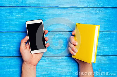 Phone versus book. A man is holding a yellow book and a phone on a blue wooden background. The choice between study and phone. Tel