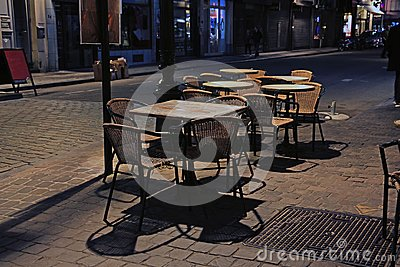 Tables and wicker chairs of an evening street cafe