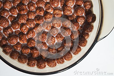 Dry healthy chocolate breakfasts in the form of balls in a plate of milk. Flakes of wheat and corn.