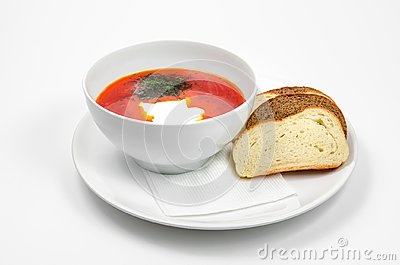 Red borscht soup with dill in white bowl.