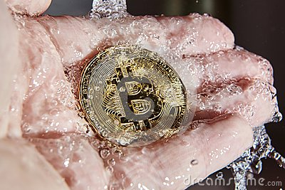 Golden bitcoin in the palm of a hand. Money laundering
