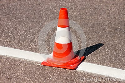 Work on road. Construction cone. Traffic cone, with white and orange stripes on asphalt. Street and traffic signs for signaling.