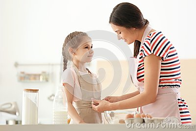Young woman helping her daughter to put on apron in kitchen. Making dough together