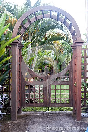 Wooden arbor with close gate in garden. Wooden arched entrance to the backyard.