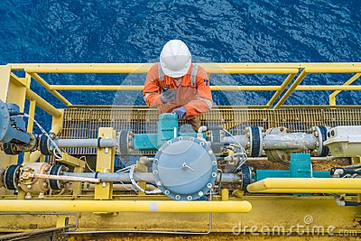 Offshore oil rig worker checking parameter of coriolis digital flow transmitter meter, instrument and electrical service.