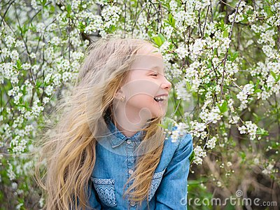 Girl with her hair down in a denim shirt in a cherry blossom garden. Portrait of laughing happy girl.