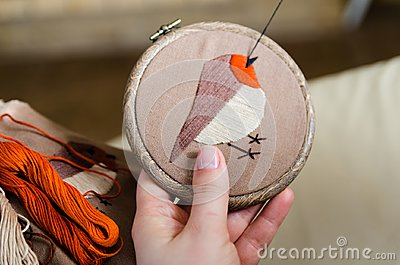 Girl embroiders a bird with a stitch. DIY concept, Hobbies, creativity, clothing and interior decoration