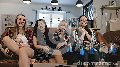 Pretty girlfriends watch and discuss movie on TV. Happy smiling female friends enjoy comedy film together 4K slow motion