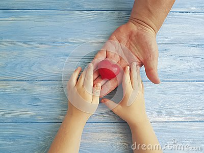 Father`s Day Hands Dad and Child giving greeting creative holding thankful Heart on a Blue Wooden Background