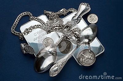 A handful of silver bullion, silverware, jewelery and old silver coins on a dark blue background