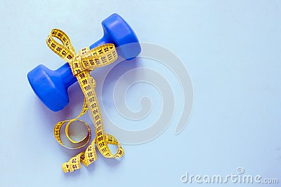 Fitness and weight loss concept. Blue dumbbell with bow of yellow centimeter on a blue background. Top view.