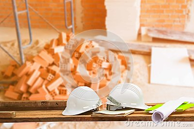 Safety helmet plastic and blueprint on wood with blur construction building site workplace background. with copy space add text