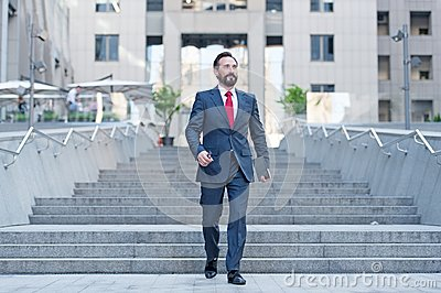 Happy business person walks downstairs in hurry movement with tablet. Young contemporary businessman walking in finance centre