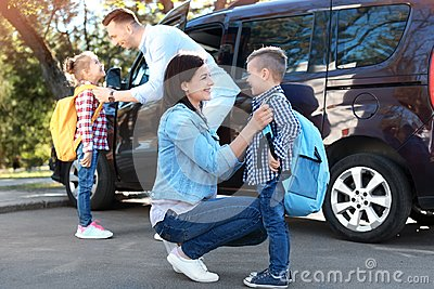 Young parents saying goodbye to their children near school