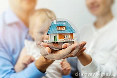 New home concept - young family with dream house scale model