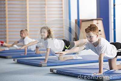 Kids exercising balancing yoga pose