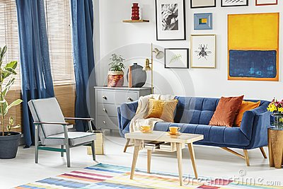 Bright and cozy living room interior with blue drapes, a sofa wi