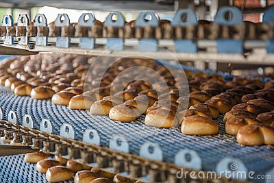 Cakes on automated round conveyor machine in bakery food factory, production line