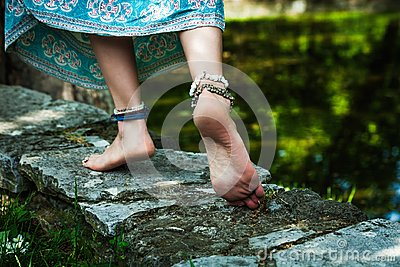 Barefoot woman walk boho fashion style with jewelry outdoor