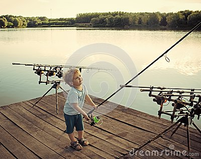 Fishing equipment. Boy fisherman with fishing rods on wooden pier