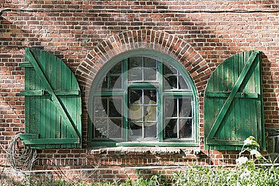 Window in a brick farmhouse with shutters in Schleswig Holstein, Germany