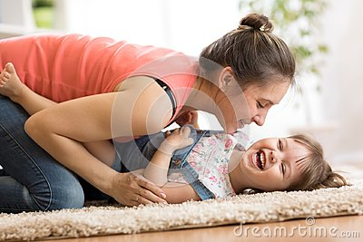 Family - mom and daughter having a fun on floor at home. Woman and child relaxing together.