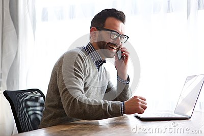 Happy man talking on cellphone in front of laptop computer