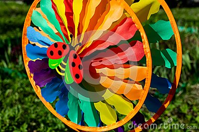 Multi colored round pinwheel in motion, in sunny garden. Big round rainbow pinwheel in motion.