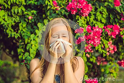 Pollen allergy concept. Young woman is going to sneeze. Flowerin