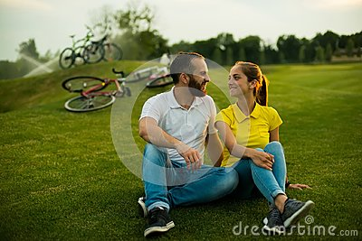Young beautiful couple sitting on grass in the park.