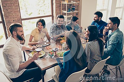 Friend`s gathering for feast. Cheerful youth is having tasty foo
