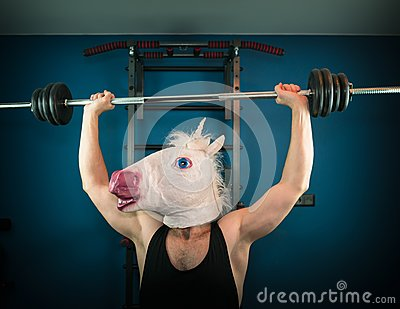 Funny man in comical mask doing sport exercise