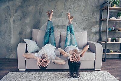 Funny couple with glasses gesturing is lying upside-down on the