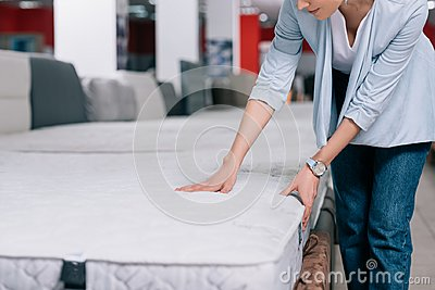 partial view of woman touching orthopedic mattress