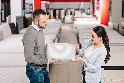 couple choosing folding mattress together in furniture store