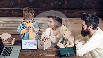Parents teaches son, wooden wall background. Boy listening to mom and dad with attention. Homeschooling concept. Parents