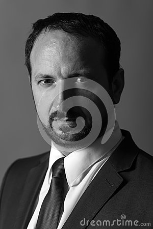 Leader settles disputes on dark grey background, black and white. Man with beard and serious face manages business.