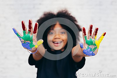 African American playful and creative kid getting hands dirty with many colors
