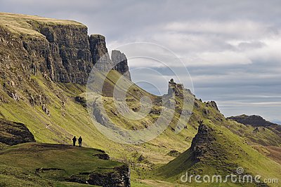 Quiraing, Isle of Skye, Scotland - Bizarre rocky landscape with two human figures standing on a cliff in the foreground