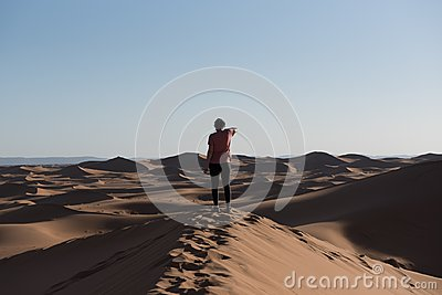 Woman in the dunes of the Sahara Dessert, Morocco