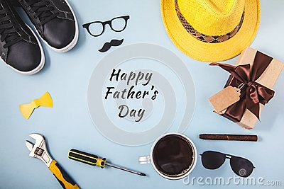 Father`s day background or card Tools Yellow hat Glasses Sneakers Cup of coffee Cigar Gift on a blue background Text Flat lay Top