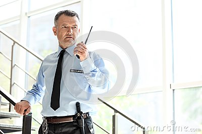 Male security guard using portable radio transmitter